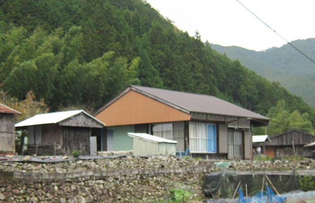 石垣の上にガンギ(赤茶色の三角形の部分)のついた民家と小屋が並ぶ。