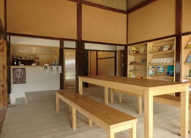 kitorasuの客室から厨房方向を見る。右手の棚には〈絵本や・ありが10匹。〉の店主によって厳選された絵本がずらり。