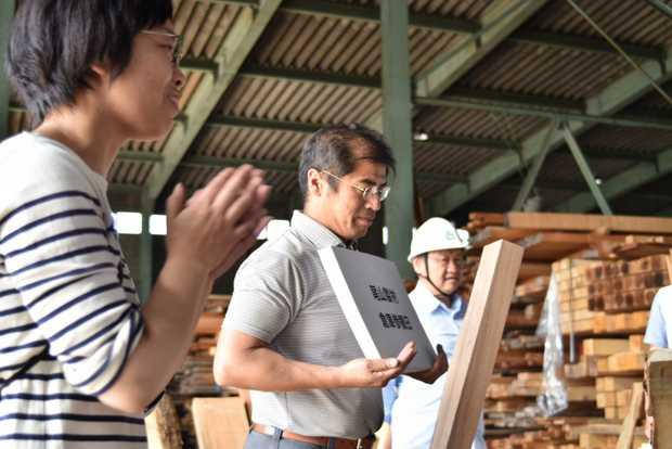 倉庫参観日の参加者にフリップを使って解説する尾山さん。(筆者撮影)