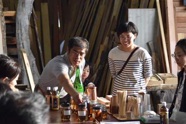 原木で香りをつけたお酒を説明する尾山さん。右はイベントを共催したD&DEPARTMENT TOYAMAの店長・進藤仁美さん。(筆者撮影)