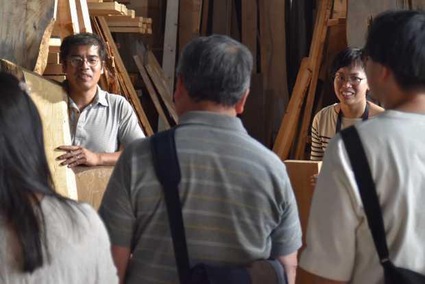 倉庫参観日で倉庫の材木を解説する尾山さん。(筆者撮影)