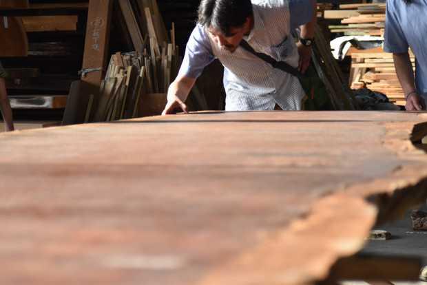 尾山製材の倉庫に保管された材木を見る参加者。(筆者撮影)