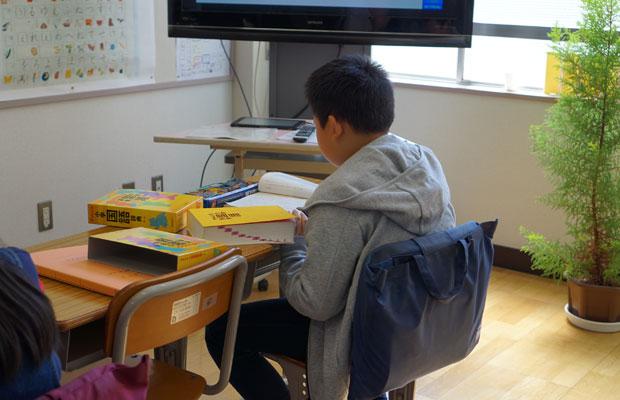 国語辞書を引きながら教科書を読む児童。