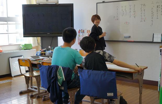 日本語で話す先生と、中国語で答える児童。辞書を引きながら互いの言葉を学んでいく。