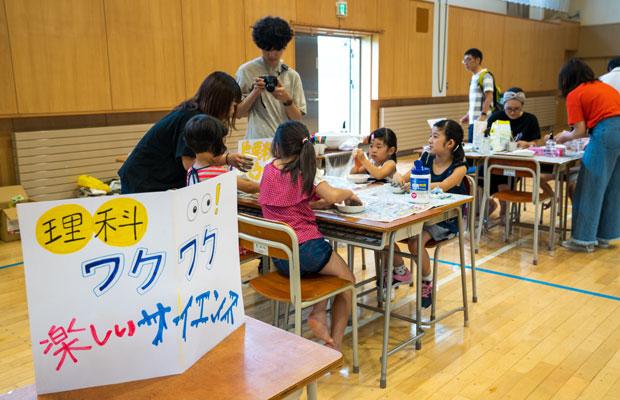 閉校になった小学校に通っていた子どもたちも集まった。「理科」コーナーで片栗粉のスライムづくりを体験中。(撮影:tacaё)