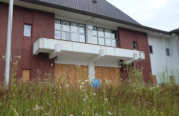 閉校後の小学校の校舎。玄関や1階の窓には板が貼られ、ひっそりと静まり返っている。