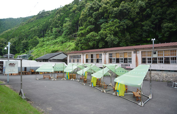 完成した竹テント。山と学校に映えています。