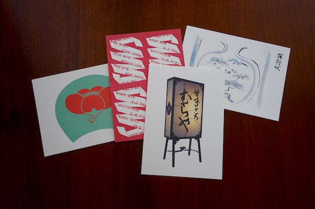 今回の企画展限定でつくられた〈セットはがき(4枚入り)〉。〈むらや〉の鉄行灯やアサヒビール包装紙の試作、パリの日本料理店〈じゅん〉のためのうちわ絵や挨拶状の試作が配されています。