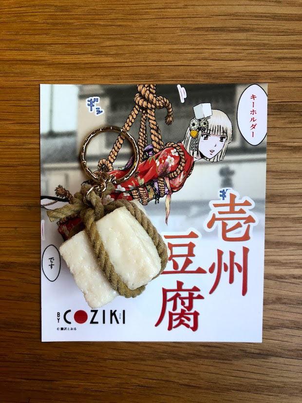 カミテンオリジナルグッズのひとつ「壱州豆腐キーホルダー」1300円(税別)※30個限定。壱岐の名物、壱州豆腐を藤沢とおるに漫画にしてもらい、カミテンでは食品サンプルキーホルダーを発売。(c) 藤沢とおる