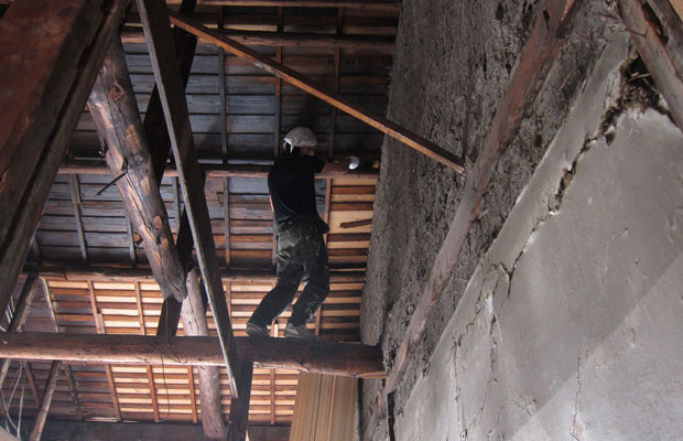 梁に乗って天井を塗装。素地の部分を黒く塗っていきます。