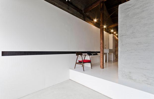 事務所に入るとモルタルのキューブのある土間空間。壁の黒いスリットにはコンセントなどが仕込んであります。