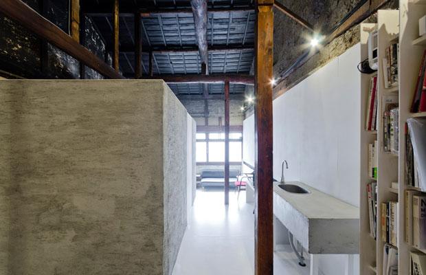 事務所スペースから土間への見返し。黒い天井と柱、モルタルのキューブとキッチン、白い床、という構成。