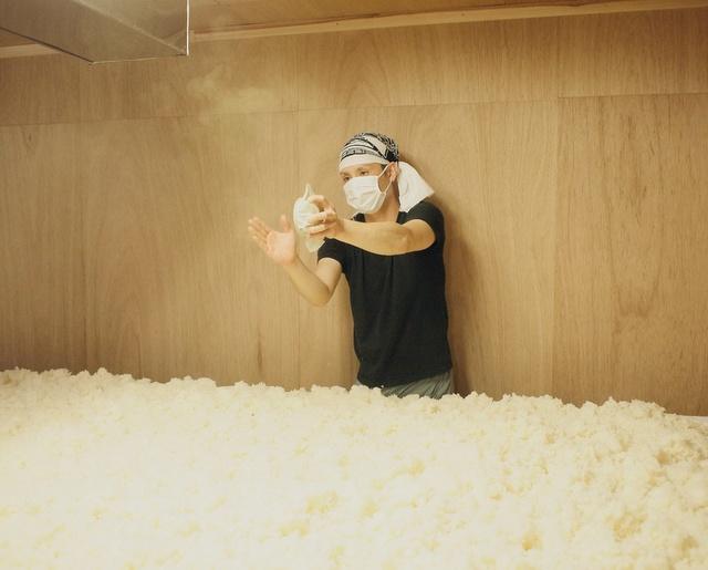 室に引き込んだ酒米を規定の温度まで下げた後、均一に広げて種麹を振っている様子。