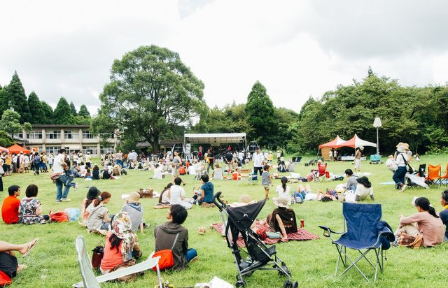 野芝に覆われ青々としたグラウンドでのんびり楽しむ観客。