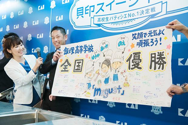 飯塚高等学校「muguet」の応援ボードを持って応援する顧問の林田先生。