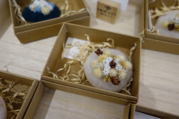 青森ヒバの木板に、青森県産の羊毛、羊毛フェルト、ドライフラワーをあしらってつくられたブローチ(福田直美さん作)