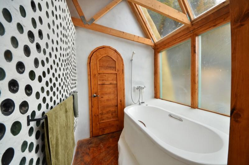 奥のかわいいドアも前坂さん作。浴槽は土台づくりから設置まで倉科さんとボランティアで行った。