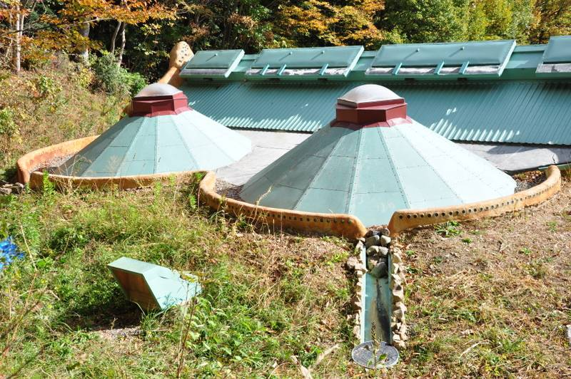 家の裏側に回ると、円墳のような屋根がふたつ。雨水を受ける堤を設け、底に敷き詰められた砂利によってろ過された雨水が地中に埋められた貯水槽に流れ込むようになっている。