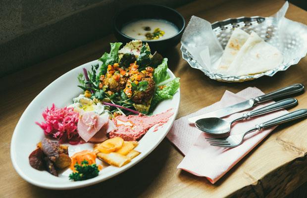「ファラフェルサンドプレート」(1200円)ファラフェル(ひよこ豆のコロッケ)と、ビーツのフムス、人参とブロッコリーのクミンソテー、長ネギと柿のマリネなど、日替わりの総菜が色鮮やかに並ぶ。ピタパン、スープつき。