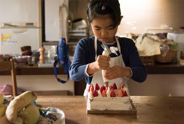 ケーキのデコレーションをする娘