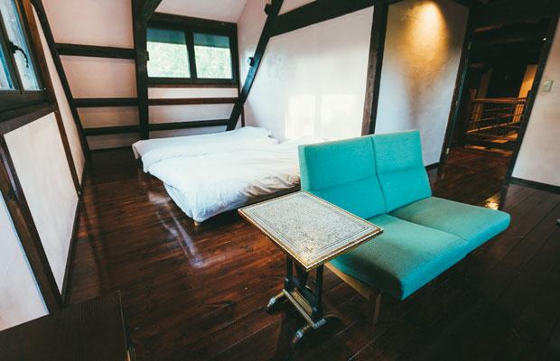 ベッドとソファ、小さなアンティークのテーブルが置かれたシンプルで過ごしやすい部屋。
