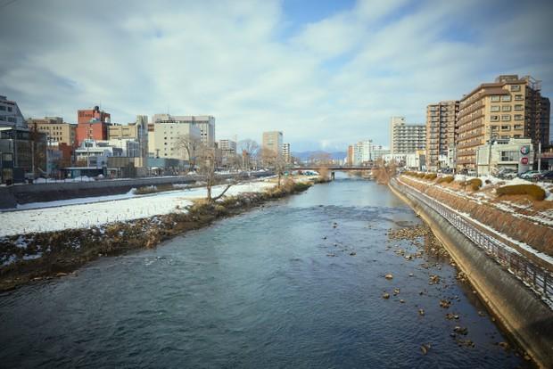 盛岡駅前の開運橋から望む北上川と岩手山は、大友監督の好きな風景のひとつ。残念ながら、撮影当日は岩手山に雲がかかっていた。