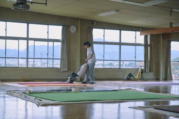 シャーリング(表面仕上げ)を行う職人さん。じゅうたんの表面を均一にするため、芝刈りのような専用機械で表面を切り揃えていく。