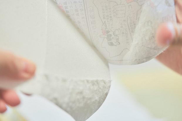 手作業で裂いて、ビニール以外の部分を取り出します。とても細かい作業。(撮影:張田亜美)