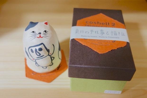起き上がり小法師〈モアイ抱き猫〉。岩手県の張子工房〈coshell2(コシェルドゥ)〉の小法師に、tomoyaさんの描いた〈moai〉をあしらってもらったもの。箱の上にパッケージされた六角形の紙は〈NOZOMI PAPER®〉で、小法師の座布団としても使用できます。