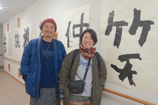 "〈HUMORABO〉の雄一さんと亜希子さん。壁に飾られた「笑」「仲」などの文字も〈のぞみ福祉作業所〉の""アーティスト""の作品。"