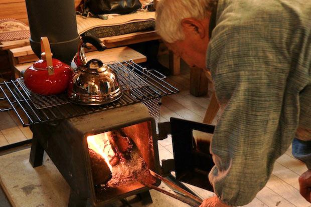 薪ストーブで火を熾す吉田さん。身近なものから生活のエネルギーをいただく山の暮らし。