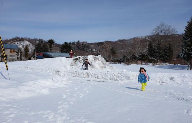家の前の雪山で遊ぶ子どもたち。休校になったけれど、一歩外に出れば、どこでも駆け回れるのはありがたい。