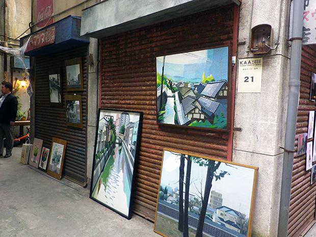 シャッター街の一区間がアーティストに与えられ作品を発表、審査される。健志さんは花と熊本の風景を描いた油絵を出品した。