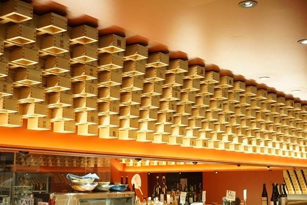 京都にできた「日本酒とおばんざいのお店 おざぶ」は、天井際にくの字に組んだ枡を設置。ライティングされた姿はかなり迫力があり、店内をよりモダンな雰囲気に演出します。