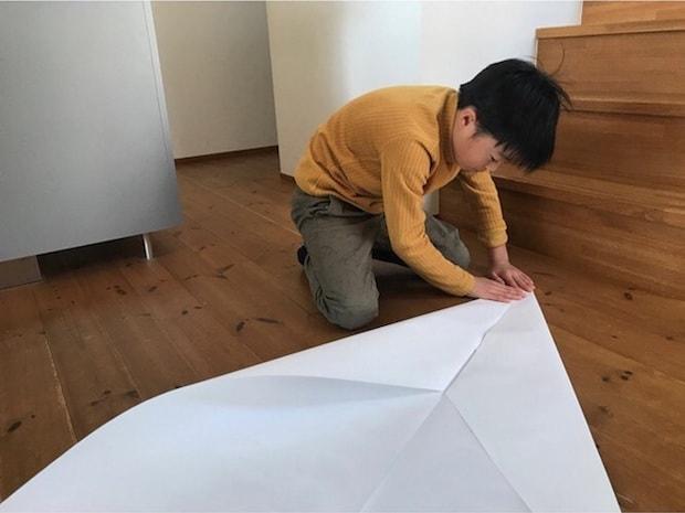 大きな紙飛行機をつくった男の子。