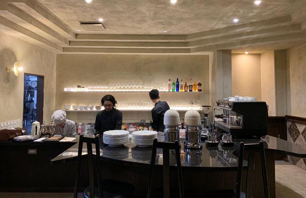 カウンター側。砂壁に包まれたミニマムでやさしい空間に、先代から受け継いだフレッシュジュースマシーン、グラス、皿が並ぶ。