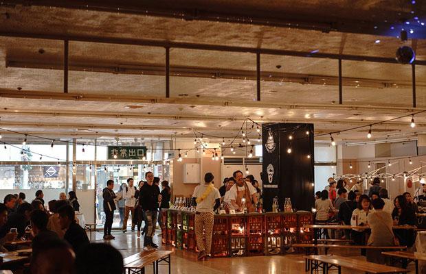 イベント「ヤナガセワインホール」会場風景。酒屋のプラスチックケースをカウンターにワインが提供される。建物に人が出入りすることで、まちに血が通うような感覚をもった。