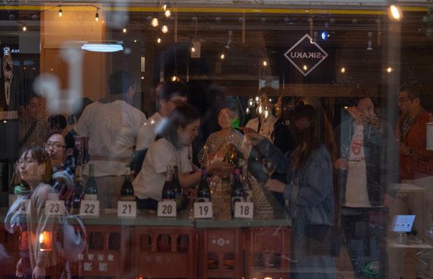 シャッターの開いた〈旧長崎屋〉。商店街の行き交う人と、室内の人がガラス越しに交差する。