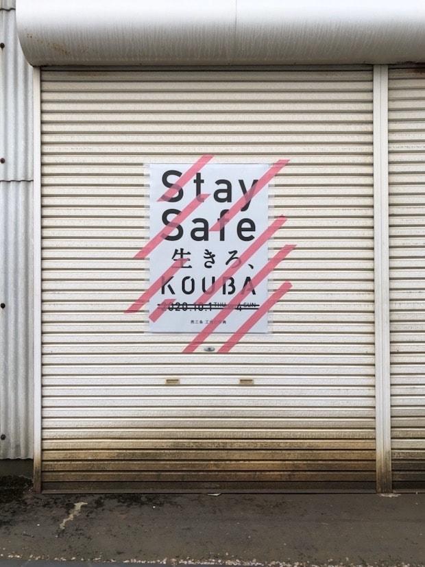 「Stay Safe 生きろ、KOUBA」と書かれたポスター