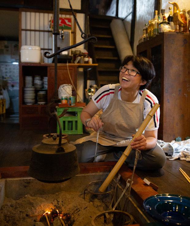 囲炉裏で火起こしをする高橋さん。このあと高橋さんは夕食の準備でキッチンへ。辺りが暗くなっていくなか、火を見つめながら過ごす時間が心地いい。