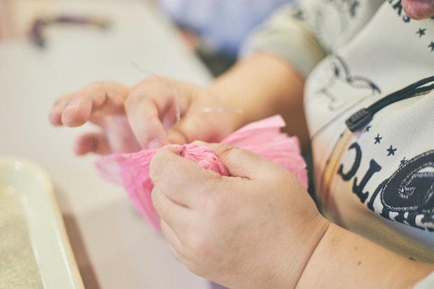 ひとつひとつの花紙から手で針金を取り外す様子。(撮影:張田亜美)
