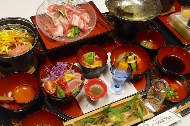 二戸の三元豚佐助のバラ・カタロース・ロースを食べ比べできるしゃぶしゃぶや、二戸の熟レ鶏で出汁をとった郷土料理のひっつみ汁などが並ぶ夕食(一例)。テーブルの上にのるのは、魚も野菜もお酒もすべて二戸で育まれたものです。