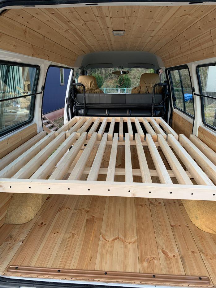 スライド式の木製ベッドがバンの荷台に自作されていた。