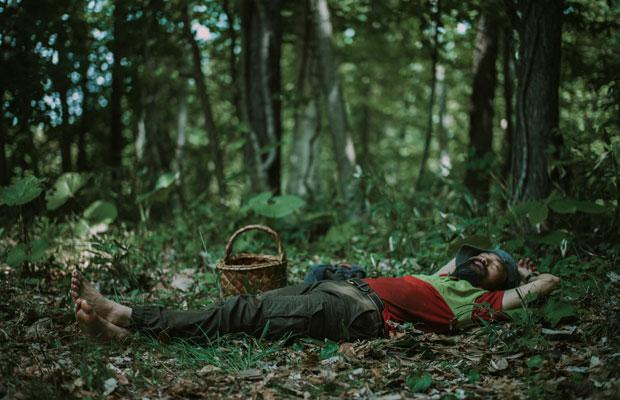 作業の合間のランチタイム。裸足で気持ち良さそうに寝そべる陣内さん。現在、キコリが家を建てるという「キコリビルダーズ」というプロジェクトを進めている。(photo:Ikuya Sasaki)