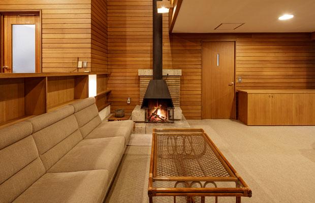 暖炉のあるリビングにはつくりつけのソファーが置かれている。壁の色は経年変化によるいい色合いとなっている。(撮影:千葉正人)
