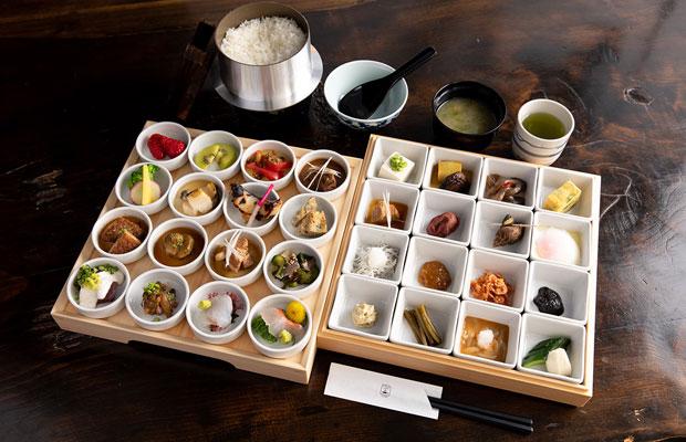32種の小鉢がずらりと並ぶ朝食(5,000円)は、レセプション近くの店で提供。端正な重箱は地木工職人・戸田勝久さんが手がけた。(写真提供:ビル泊)