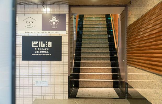 ビルの入口に設置されたロゴが目印。ありふれたビルのエントランスと客室のギャップに驚かされる。