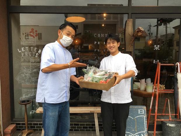 信州大学の学生に野菜を渡す高橋さん。学生グループに野菜を進呈したのは、野菜不足になりそうな一人暮らしの学生さんに喜ばれるのでは、という思いから。