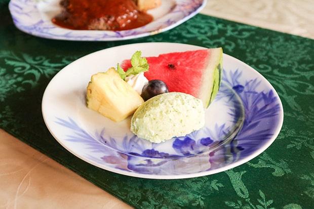 きゅうりアイスと季節のフルーツ。お皿は店主が骨董市などを回って選んだものだそう。店内にも江戸や明治の古い器が並ぶ。