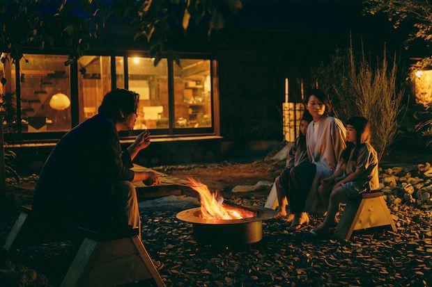 焚き火を囲んで座る男女と子供2人